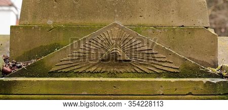 Eye Of Providence Or All-seeing Eye Carved In Sandstone, Weathered And Grown With Moss And Lichens