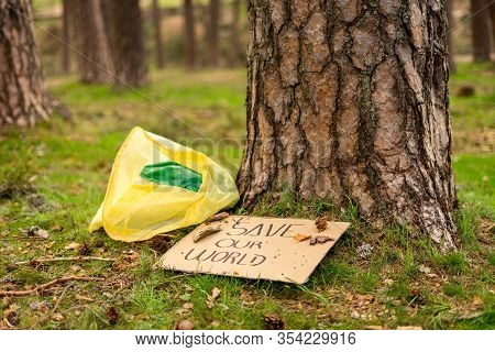 View Of A Cardboard Banner On The Ground With An Environmental Message Next To A Plastic Bag At The