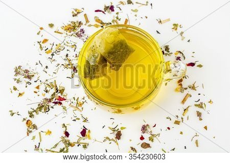 Two Tea Bags Of Green Tea In Glass Mug With Heap Of Dry Tea Leaves On A White Background. Organic He