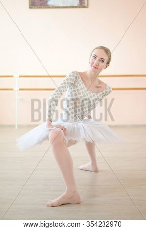 A Very Flexible Ballerina In A Tutu Stands In A Plie In A Class With Ballet Machines. Incredibly Pla