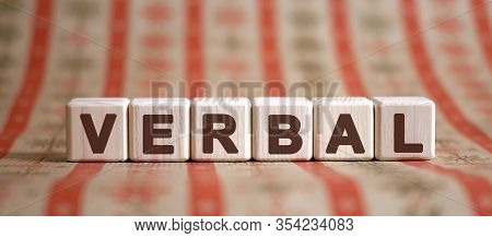 Verbal Word On Wooden Cubes On A Color Background