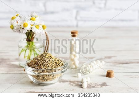 Bottlles Of Homeopathic Globules With Chamomile Flowers On Wooden Table. Alternative Medicine Concep