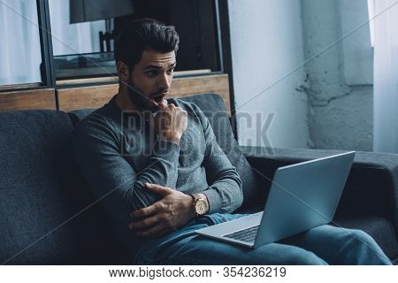 Shocked Handsome Man Watching Pornography While Sitting On Couch In Living Room