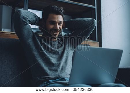 Handsome Man Smiling While Watching Pornography On Laptop On Sofa