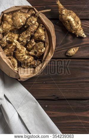 Several Jerusalem Artichoke Tubers In A Paper Bag On A Wooden Table With Copy Space. Helianthus Tube