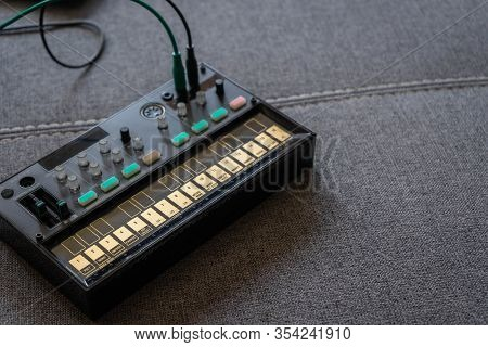 Close Up View Of Small Black Fm Synthesizer With Patch Cable On Top Of A Sofa With Space To The Righ