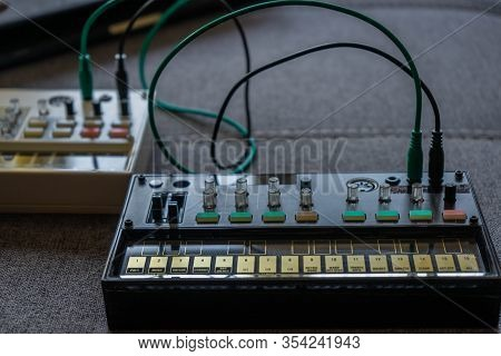 Close Up View Of A Small Black Fm Synthesizer With Patch Cables With Another Synth Behind It On Top