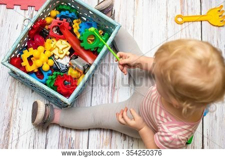 Small Box Filled With Childrens Small Toys For Education. View From Top. Little Kid Sits Near Box Of