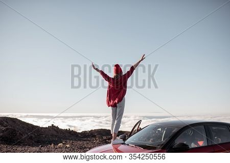 Young Woman Dressed In Red Enjoying Rocky Landscapes Above The Clouds, Standing On The Car Highly In