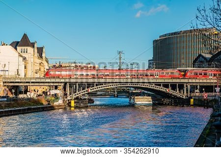 Berlin, Germany - December, 2019: Business Downtown, Red Train And Bridge Over Spree River.