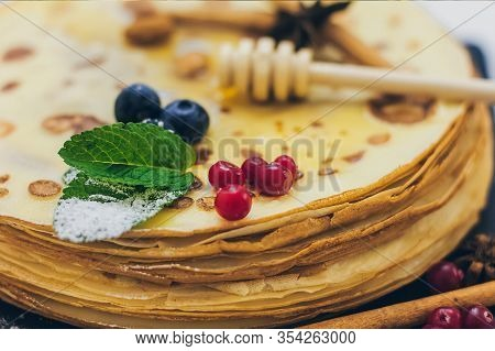 Plate Of Pancakes Dripping With Honey With Cranberries And Blueberries, Cinnamon Sticks. Shrovetide