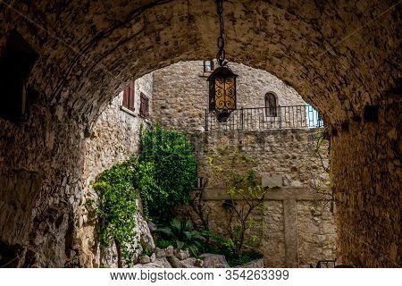 A Tunnel-like Passage Of An Old Medieval Town With A Crafty Metal Lantern Hanging In The Middle (Èze