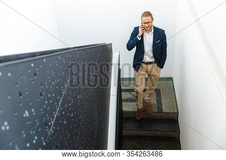 Image of handsome young pleased businessman indoors walking by stairs talking by mobile phone.