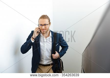 Image of smiling young businessman indoors walking by upstairs talking by mobile phone.