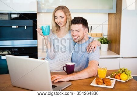 Portrait of a smiling loving couple having breakfast while sitting at the table in a kitchen at home and looking at laptop computer
