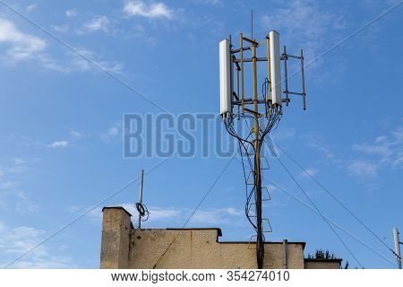 Cellular Network Antena Repeater On A Building Roof Against The Blue Sky.