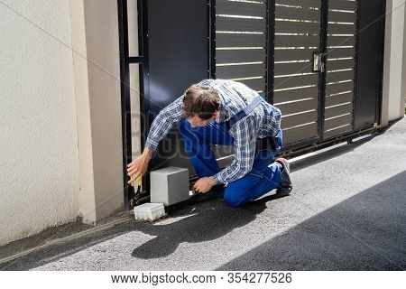 Repairman Fixing Broken Automatic Door In Building