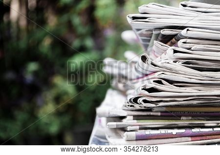 Newspapers Folded And Stacked On The Table With Garden. Closeup Newspaper And Selective Focus Image.