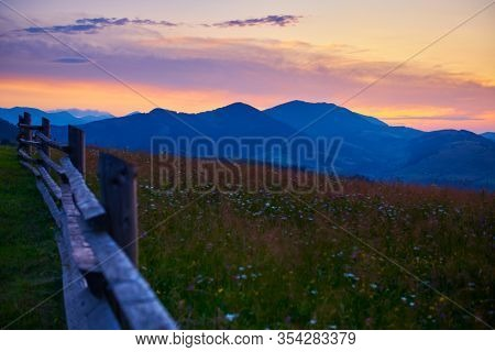 sunset and wooden fence along pasture in the ranch, nature, summer landscape in carpathian mountains, spruces on hills, beautiful cloudy sky