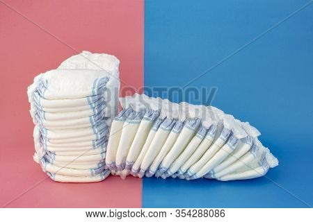 Diapers Stack With Some Diapers Falling On The Right Side On A Blue And Pink Background