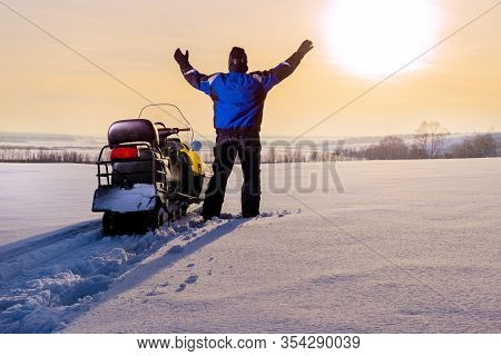 Snowmobile Adventure. Man Standing On Snowy Mountain In Winner Pose With Raised Hands Enjoying View