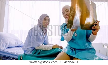 Muslim Female Doctor Analysing Disease To Patient At Hospital Room.