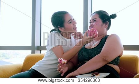 Young Woman Suggesting Chubby Woman To Eat Apple In The Room.