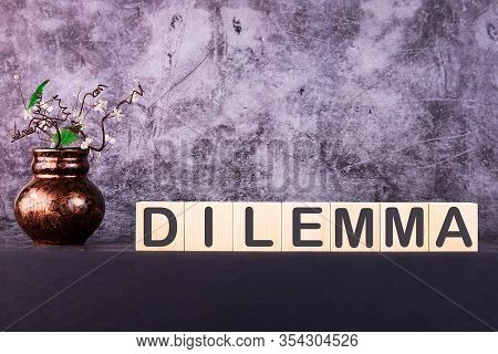 Word Dilemma Made With Wood Building Blocks On A Gray Background