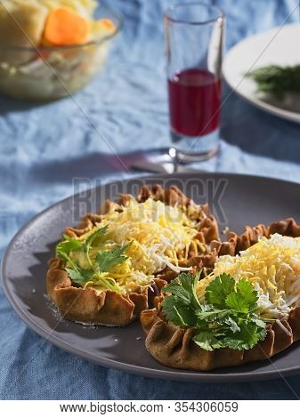 Karelian Pirakka Pies Located On A Gray Plate. Nearby Is A Fermented Beetroot Juice And A Cup With S