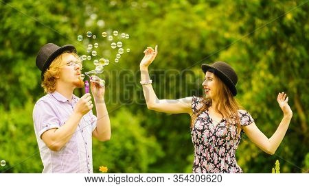 Happy Funny Hipster Couple Playing Together Blowing Soap Bubbles Outdoor In Spring Park.