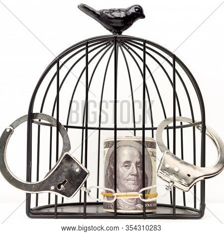 Closed Handcuffs Hang On The Bird Cage With Money. The Concept Of Imprisonment For A Bribe