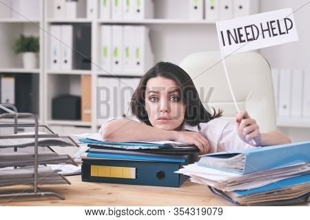 Portrait puzzled young female lawyer swamped with paperwork sitting at table with folders and holding I NEED HELP sign
