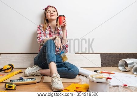 Dreamy Girl Painter Relaxing On Floor With Cup Of Coffee. House Remodeling And Interior Renovation C