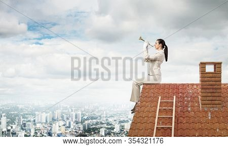 Attractive Young Woman Playing Music On Roof Of Building. Brave Businesswoman In White Business Suit