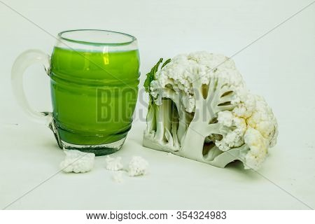 Close Up Shot Of Fresh Cauliflower Juice In A Glass Along With Raw Cut Cauliflower.