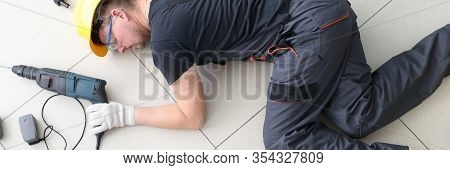 Unconscious Man Lying At Floor With Tools And Instruments. Health Problems Of Person, Accident At Jo