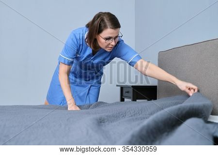 Middle Aged Female Professional Maid Making Bed In Hotel Room. Service, Cleaning, Staff, Hotel Conce