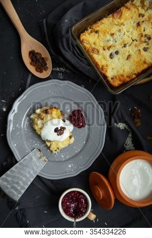 Cottage Cheese Casserole With Raisins On A Gray Plate, Poured Sour Cream On Top. Flat Lay, Top View.