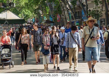 Barcelona, Spain - May 16, 2017: Unknown People Walking On The Famous La Rambla Street In Center Of