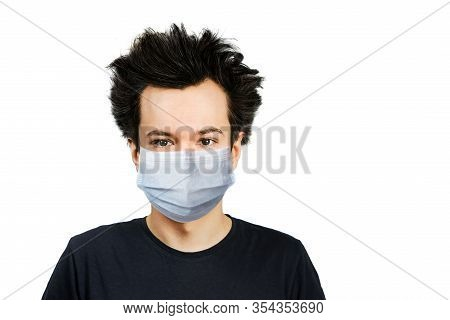 Unhappy, Mad Young Man Wearing A Protective Face Mask Prevent Virus Infection Or Pollution On White