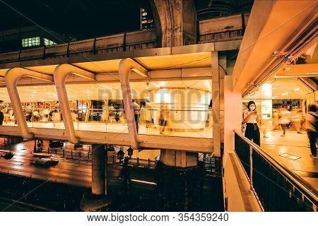Bangkok, Thailand: People In Flu Masks Walking Through Concrete Flyovers For Pedestrians, In Lights