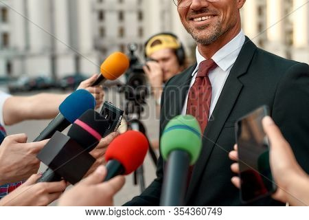 Cropped Portrait Of Smiling Man In Suit Giving Interview To Reporters. People Making Interview Using