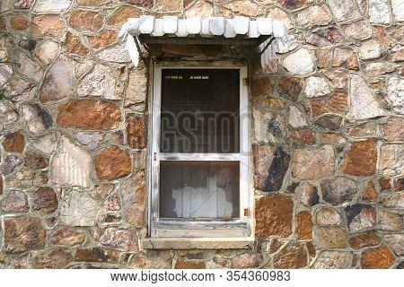 A Vintage Shutter Screen Window On A Retro Stone Wall Farm House