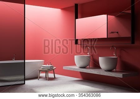 Corner Of Spacious Bathroom With Bright Red Walls, Stone Floor, Comfortable White Bathtub, Glass Wal