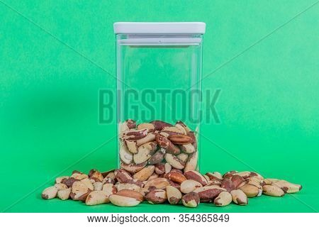 Brazil Nuts Raw Outside And Inside A Transparent Plastic Container With A Green Background, Also Cal