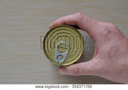 Hand Of An Adult Man Holds A Can Of Canned Food. Closed Tin Can With Open Key In Hand. A Mans Hand H
