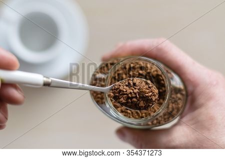 Glass Jar With Coffee In A Hand. A Hand Holds A Spoon Full Of Instant Coffee. Pile Of Instant Coffee