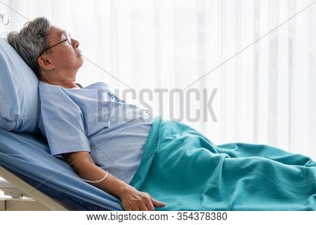 Asian Patient Man Lying Down On Hospital Bed In The Hospital Room.