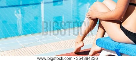 Tanned Woman Is Sitting By The Swimming Pool And Applying Sunblock To Protect Her Skin From Sunburn.