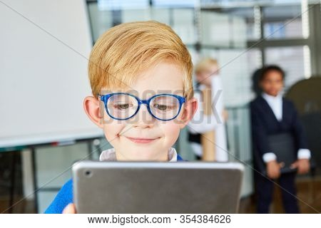 Smiling Child with a Tablet Computer in Elementary School